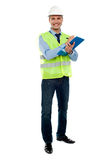 Full length portrait of handsome architect. Writing key notes on clipboard stock image