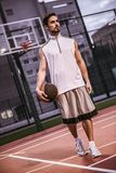 Handsome basketball player. Full length portrait of handsome basketball player standing with a ball on basketball court outdoors royalty free stock photography