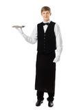 Full length portrait of handsome elegant waiter holding empty tr stock photography