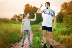 Full length portrait of handsome father and little daughter showing their muscles, looking at camera and smiling outdoor. Full length portrait of handsome father royalty free stock images