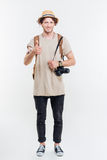 Full length portrait of handsome male tourist looking at camera. And showing thumbs up gesture isolated on a white background Stock Photos