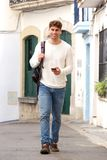 Full length handsome man walking with cellphone with backpack and headphones Stock Image