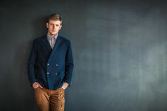 Full length portrait of handsome serious man standing against gr. Ey wall background with copy space Stock Photography