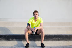 Full length portrait of handsome sports man sitting on concrete stairs with copy space area on sides while resting after jog Stock Photos