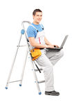 Full length portrait of a handy man with a laptop sitting on a l. Adder, isolated on white background Stock Images