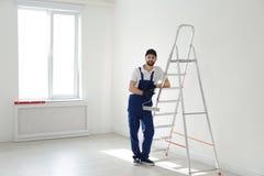 Full length portrait of handyman with roller brush near ladder indoors. Professional construction tools. Full length portrait of handyman with roller brush near royalty free stock photos