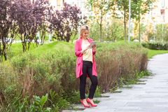 Full length portrait of happy beautiful young successful blogger businesswoman in elegance style standing on green park, holding. Tablet with toothy smile and stock photo