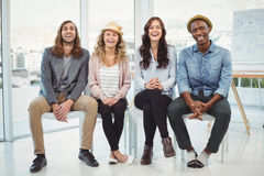 Full length portrait of happy business people sitting on chair Stock Photo