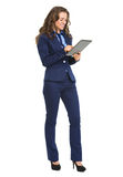 Full length portrait of happy business woman working with tablet Royalty Free Stock Image
