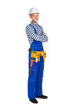 Full length portrait of happy construction worker in uniform and. Tool belt isolated on white background. Crossed arms Stock Image