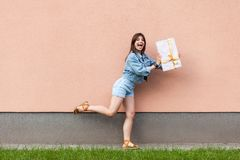 Full length portrait of happy excited beautiful woman in casual jeans denim style in summertime standing near sandybrown wall