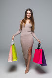 Full length portrait of a happy excited woman in dress standing and holding colorful shopping bags isolated on a grey background Stock Photography