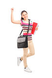 Full length portrait of a happy female student holding notebooks Royalty Free Stock Photo