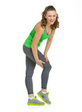 Full length portrait of happy fitness woman checking leg muscles Stock Photos