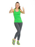 Full length portrait of happy fitness woman showing thumbs up Stock Image