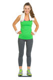Happy fitness young woman standing on scales Royalty Free Stock Image