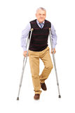 Full length portrait of a happy gentleman walking with crutches Royalty Free Stock Photos