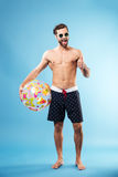 Full length portrait of a happy guy holding beach ball. Full length portrait of a happy excited guy holding beach ball and showing thumbs up gesture isolated stock photography