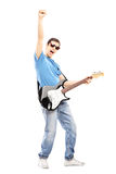 Full length portrait of a happy guy playing on an electric guita Stock Images