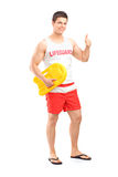 Full length portrait of a happy lifeguard on duty giving a thumb Stock Photos