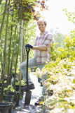 Full-length portrait of happy man holding spade at garden Royalty Free Stock Image