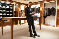 Full length portrait of happy man in suit holding  smartphone. Full length portrait of happy man in suit standing in a shop and holding  smartphone while looking Royalty Free Stock Photo