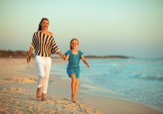 Happy modern mother and child on seacoast in evening walking royalty free stock image