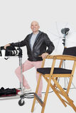 Full length portrait of a happy senior photographer with equipments in studio royalty free stock photo
