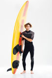 Full length portrait of a happy surfer holding surf board. Full length portrait of a young happy surfer holding surf board isolated on the white background Royalty Free Stock Images