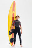Full length portrait of a happy surfer holding surf board. Full length portrait of a young happy surfer holding surf board isolated on the white background Stock Images