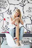 Full-length portrait of happy teenage girl with skateboard sitting on study table at home Royalty Free Stock Images