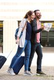 Happy tourist couple walking with map and suitcases. Full length portrait of happy tourist couple walking with map and suitcases Stock Images