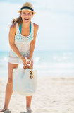 Full length portrait of happy woman in hat and with bag on beach Stock Image