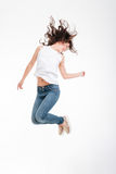 Full length portrait of a happy woman jumping. Isolated on a white background stock image