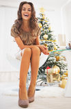 Full length portrait of happy woman sitting near christmas tree Royalty Free Stock Photography