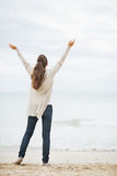 Full length portrait of happy woman in sweater rejoicing on beach Stock Photo