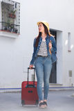 Full length happy woman walking on street with luggage and hat Stock Images