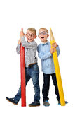 Full length portrait happy young boys in glasses and bowtie posing near huge colorful pencils. Educational concept. Isolated over Royalty Free Stock Image