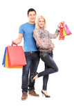 Full length portrait of a happy young couple holding shopping bags Royalty Free Stock Images