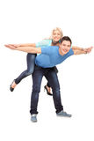 Full length portrait of  a happy young couple posing piggyback Royalty Free Stock Photography