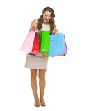 Full length portrait of happy young woman checking shopping bags Royalty Free Stock Photo