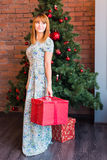 Full length portrait of happy young woman decorating christmas tree with christmas ball Royalty Free Stock Photos