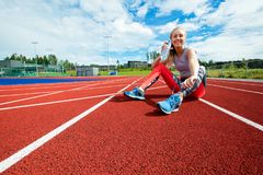 Happy Young Woman Drinking Water On Running Tracks. Full length portrait of happy young woman drinking water while sitting on running tracks Stock Photography