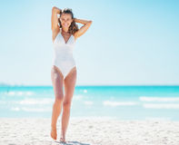 Full length portrait of happy young woman relaxing on beach. Full length portrait of happy young woman in white swimsuit relaxing on beach royalty free stock image