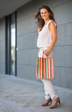 Full length portrait of happy young woman with shopping bag. On the mall alley Royalty Free Stock Photography