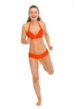 Full length portrait of happy young woman in swimsuit running Royalty Free Stock Photos
