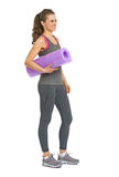 Full length portrait of healthy woman with fitness mat Stock Photo