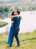 The full-length portrait of the hugging and kissing couple at the background of the river. Royalty Free Stock Photo