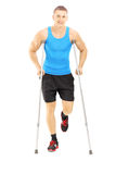 Full length portrait of an injured male athlete with crutches Stock Images