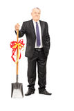 Full length portrait of an investor holding a shovel with ribbon Royalty Free Stock Image